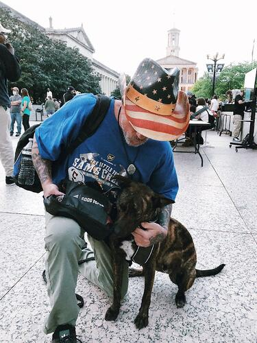 Man in American Flag Hat with Dog and Pet Pack at Good Packs distribution event in Nashville